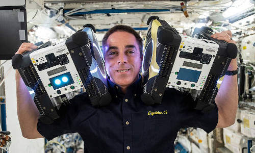 Astronaut Chris Cassidy poses with two Astrobee robotic assistants.